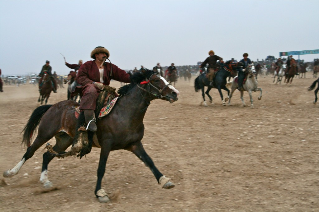 An Afghan Buzkashi player with the Buz (carcass) riding toward the flag at this end of the Buzkashi field.  Mazar-i-Sharif, Afghanistan 2007