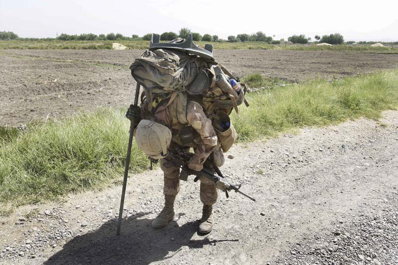 There is nothing easy about opoerating on foot outside the wire when you have to carry everything on your back - especially if you are from the 81mm mortar platoon. Photo by David Guttenfelder