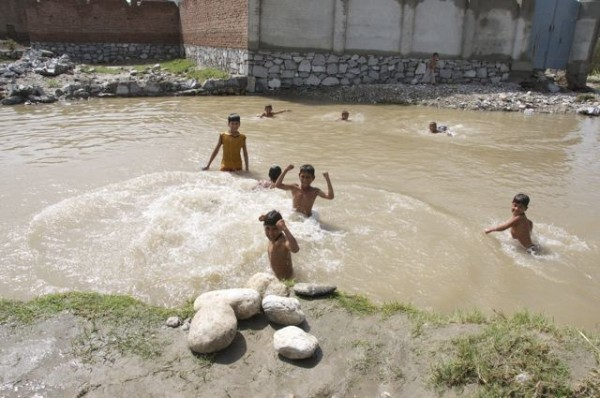 Local kids playing in a pool created by the flood waters